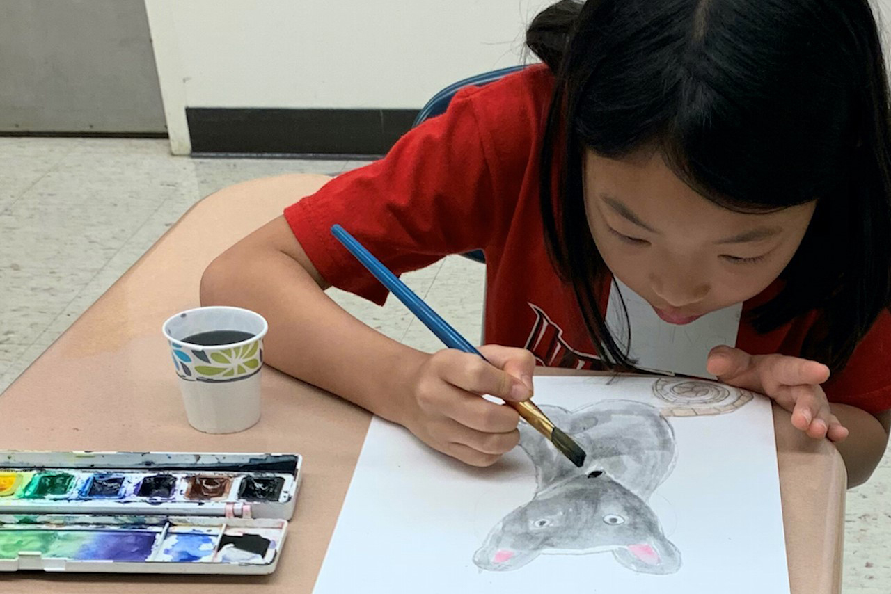 Girl painting a mouse during a Saturday visual arts class