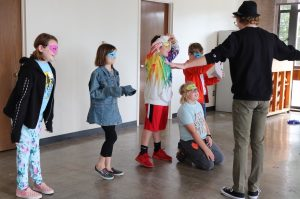 Students wearing paper theatrical masks while participating in a creative drama class in 2019