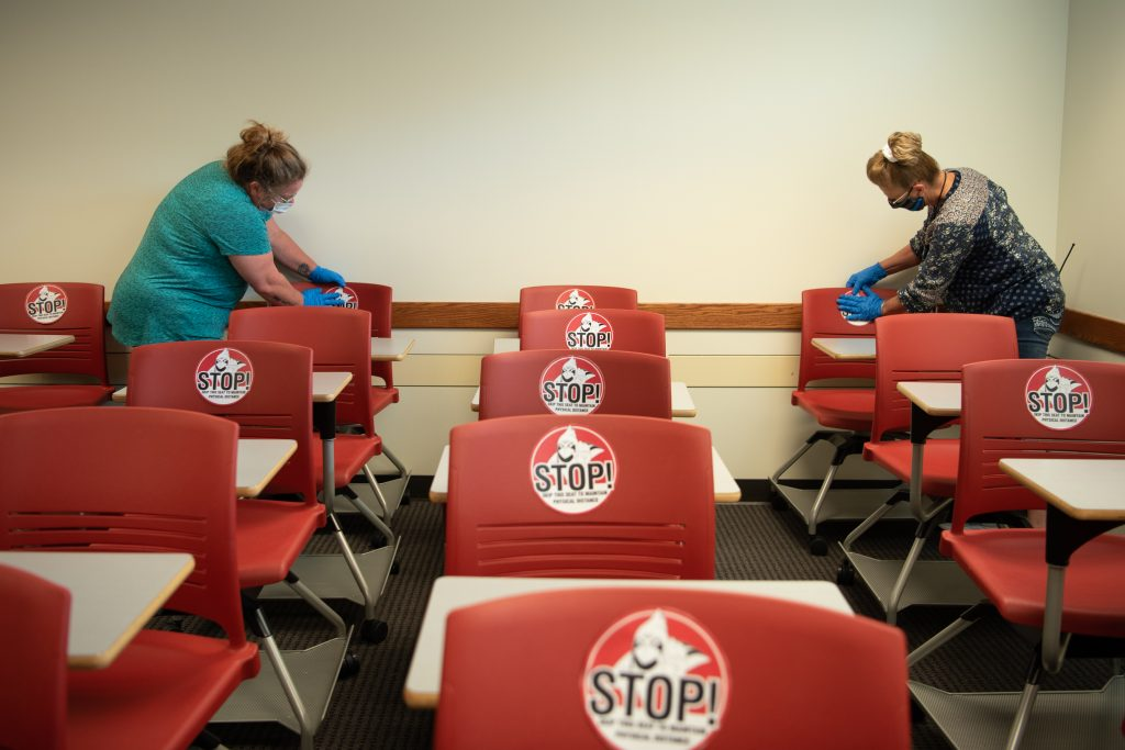 Workers place stickers on chairs