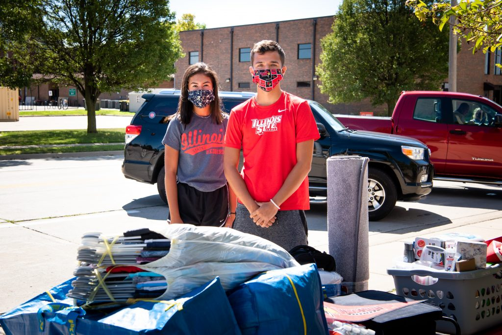Illinois State students pose next to their belongings at move-in.