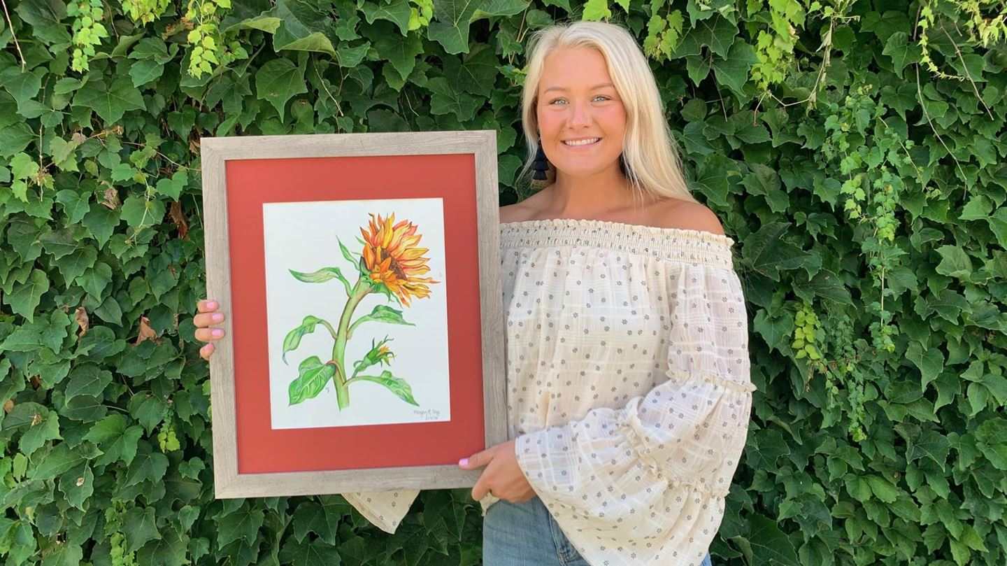 woman holding a painting of a sunflower