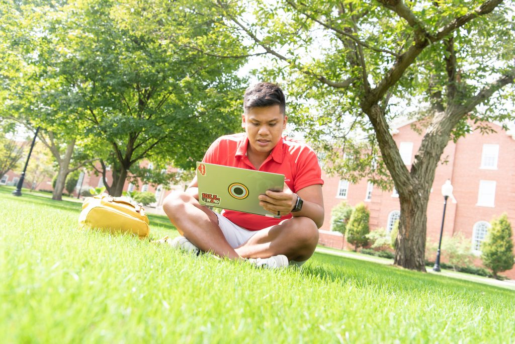 Micor enjoys the fall weather by relaxing in the grass on the Quad.