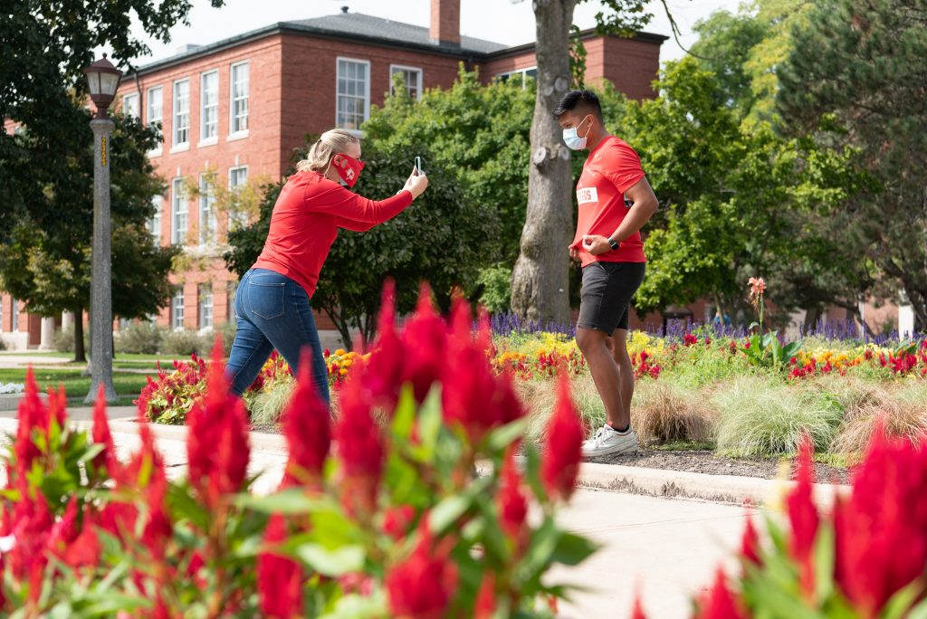 Trademark and Licensing graduate assistant Sara Engstrom does a photo shoot for new apparel with Adrian on the Quad. Adrian is a brand ambassador for University Marketing & Communications.