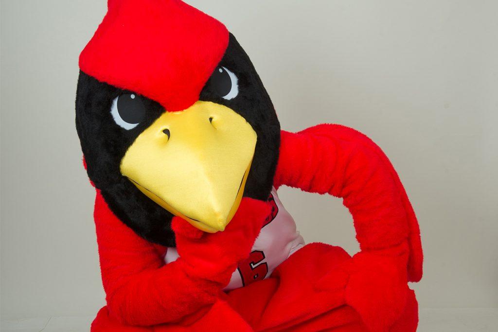 Reggie Redbird with his right hand on his beak