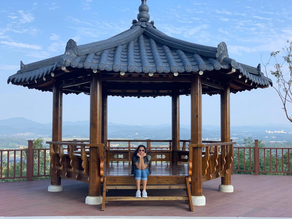 study abroad student sitting on the steps of a gazebo