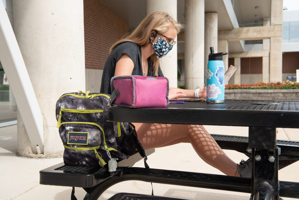 Student working at picnic table