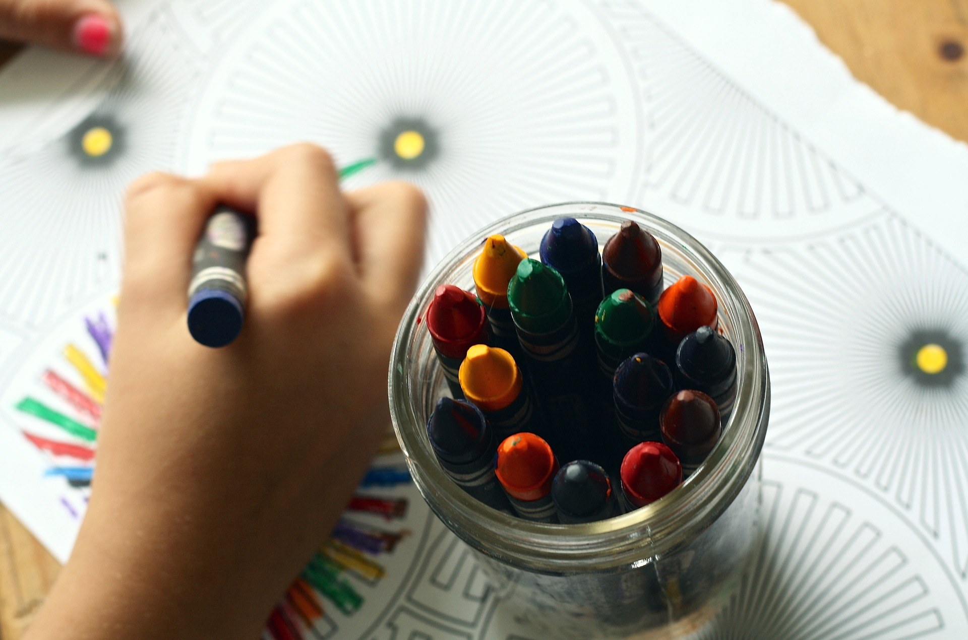 a child drawing on paper with crayons, which are being held in a cup