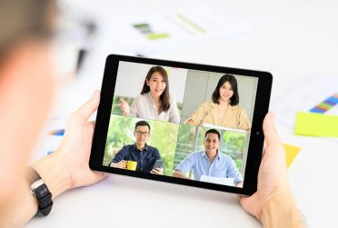 Person using a tablet to virtually meet with other people.