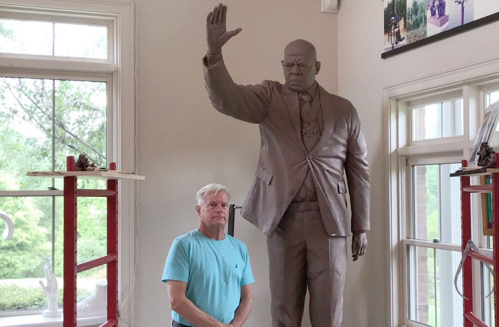 Man stands with statue