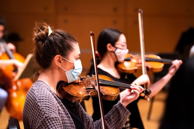 Female students in masks playing violins.