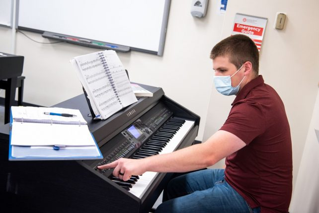 Male wearing a mask while playing an electronic keyboard.