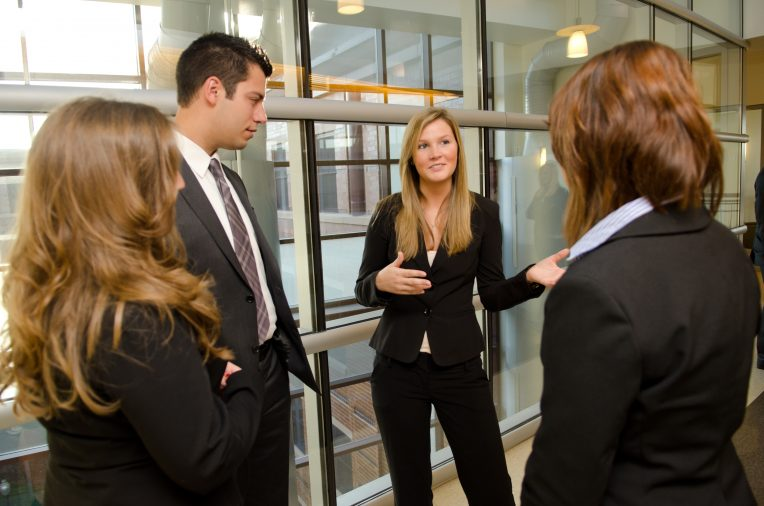 People in business attire standing, laughing, and talking