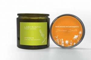 Green candle, Labyrinth Made Goods and one orange candle, hand poured and packaged by women at Labyrinth, a YWCA.