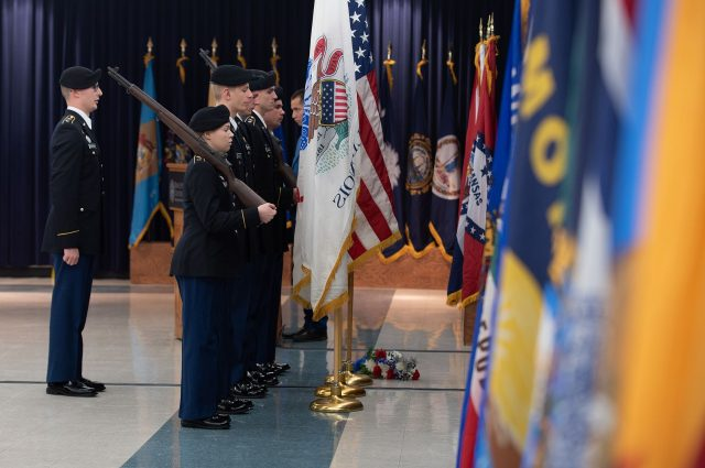 Military members stand guard at a set of flags