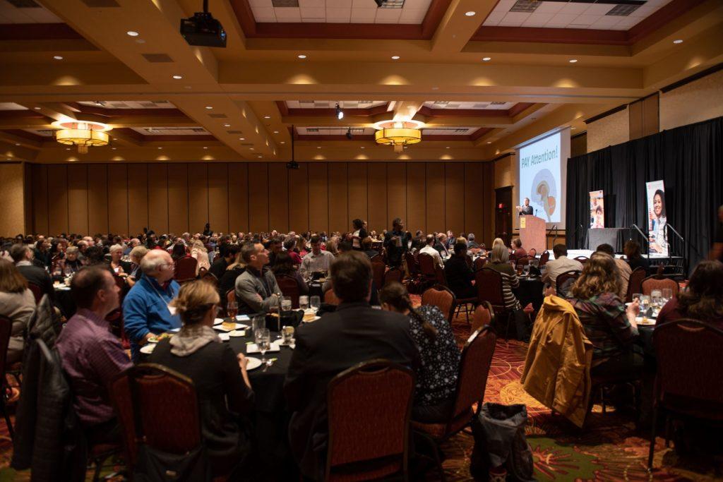 people at tables watching symposium keynote speaker