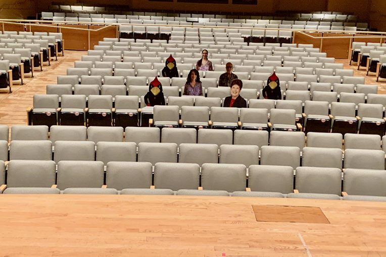 Image of Concert Hall with cutouts of Reggie and individuals filling the seats