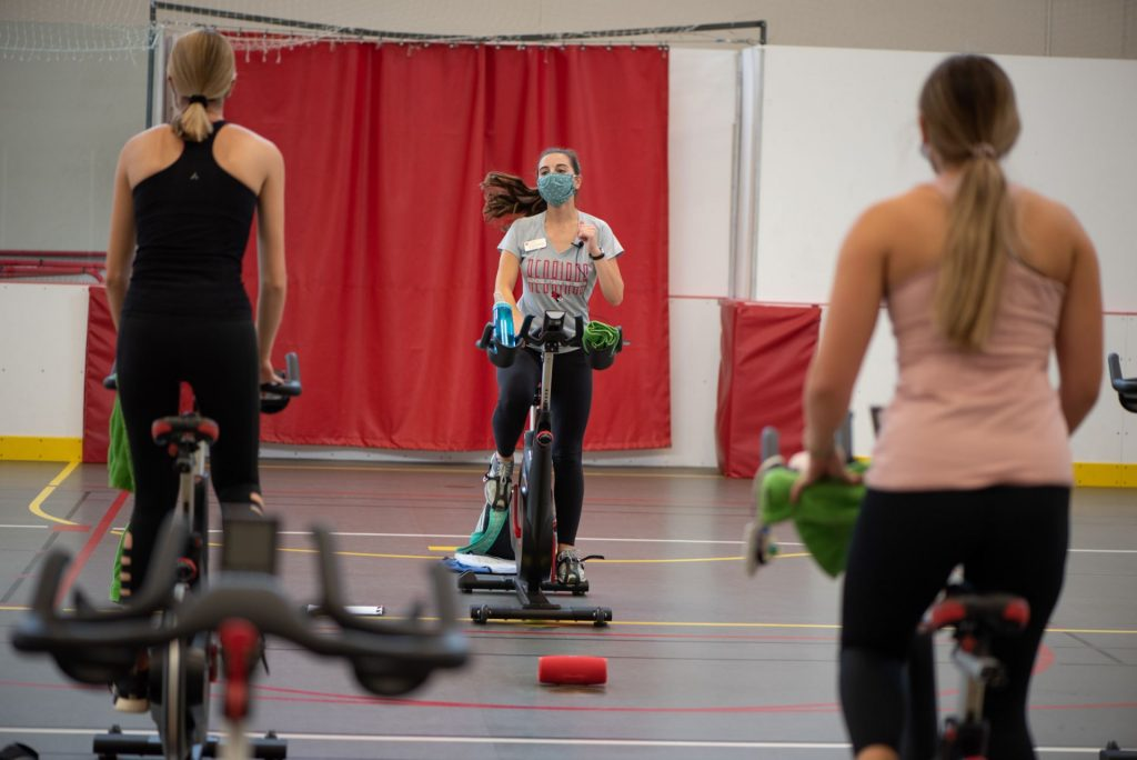 Woman teaches a cycling course as two female riders look on