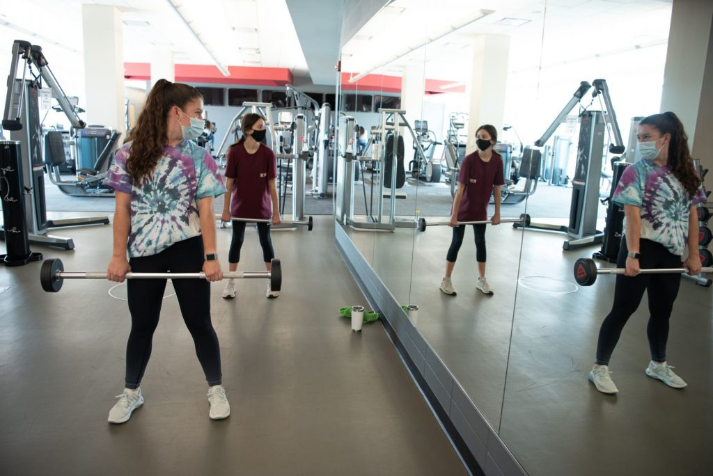 Students lift weights in front of mirror
