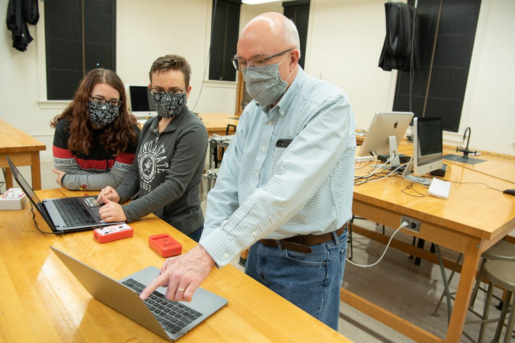 Professor works with this students in a lab