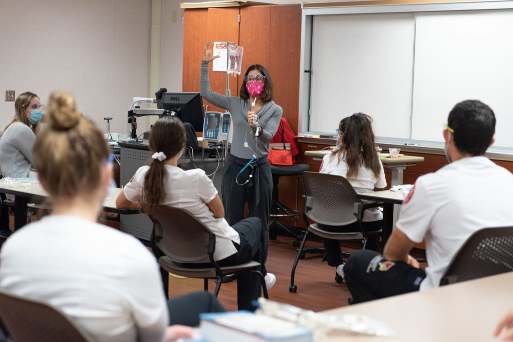 Professor demonstrates placing an IV to her students.