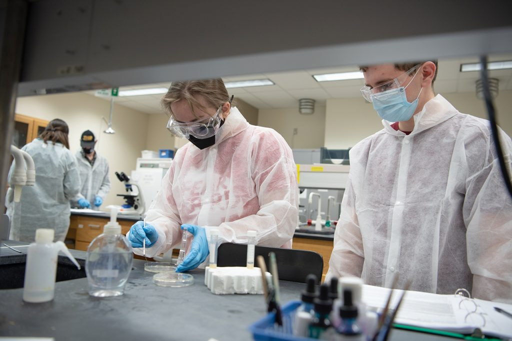 Students in lab coats look at a petri dish in a science lab