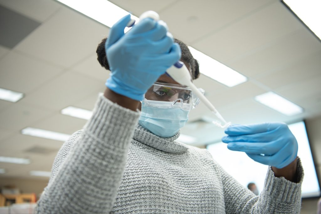 Student uses syringe in lab