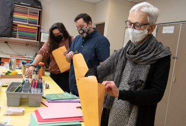 From right to left, Judith Briggs, AJ Kepa, and Katie Barko stuff packets with art supplies for the Saturday kids' art classes.
