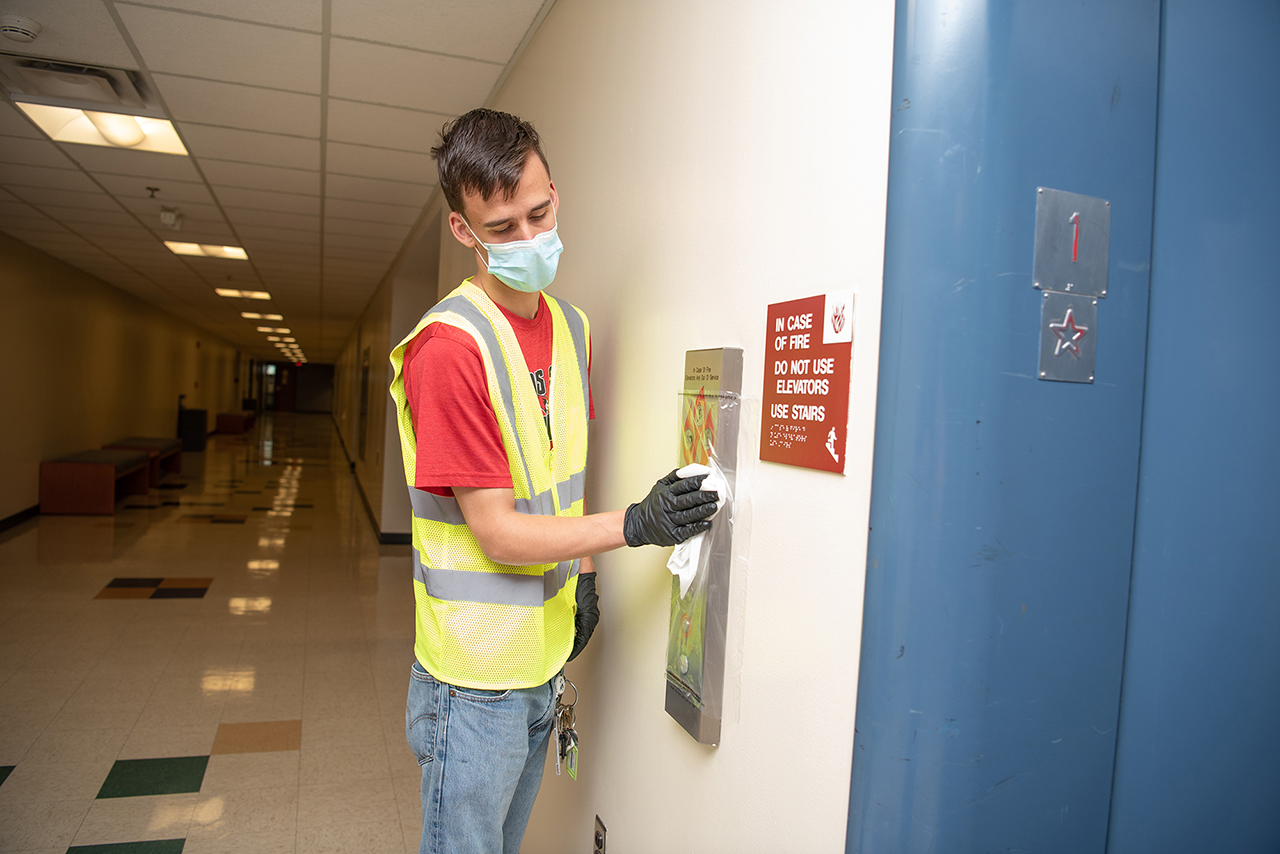 A BSW sanitizes an elevator call box.