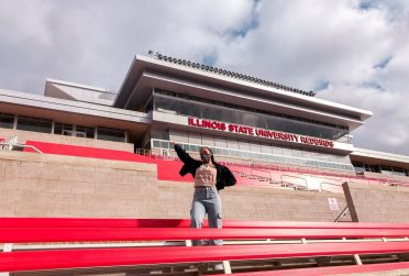 Redbird Rep student influencer poses in the stands at Hancock Stadium