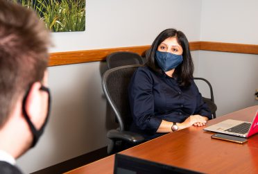 Woman in a mask during an interview with another individual