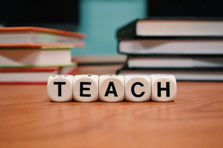 The word TEACH displayed with die on a table