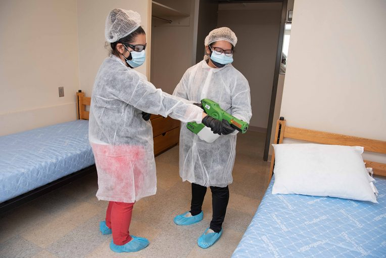 Two BSWs sanitize a room.