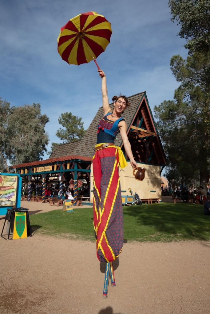 performer standing on stilts in costume
