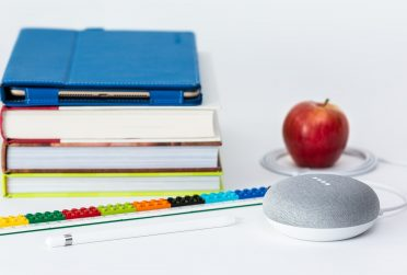 A stack of book with an apple and speaker