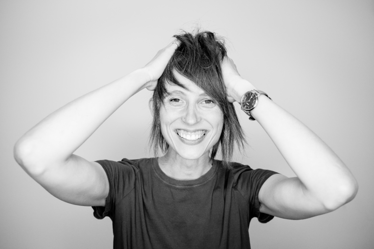 Woman smiling with hands on her head