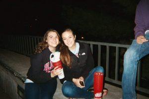 Two women sitting outside at night