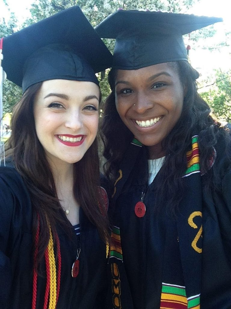 Two women smiling in graduation regalia.