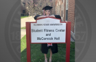 student in cap and gown posing behind sign