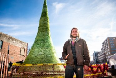 Alum and artist Jason Mack stands before his 31-foot glass Christmas tree.