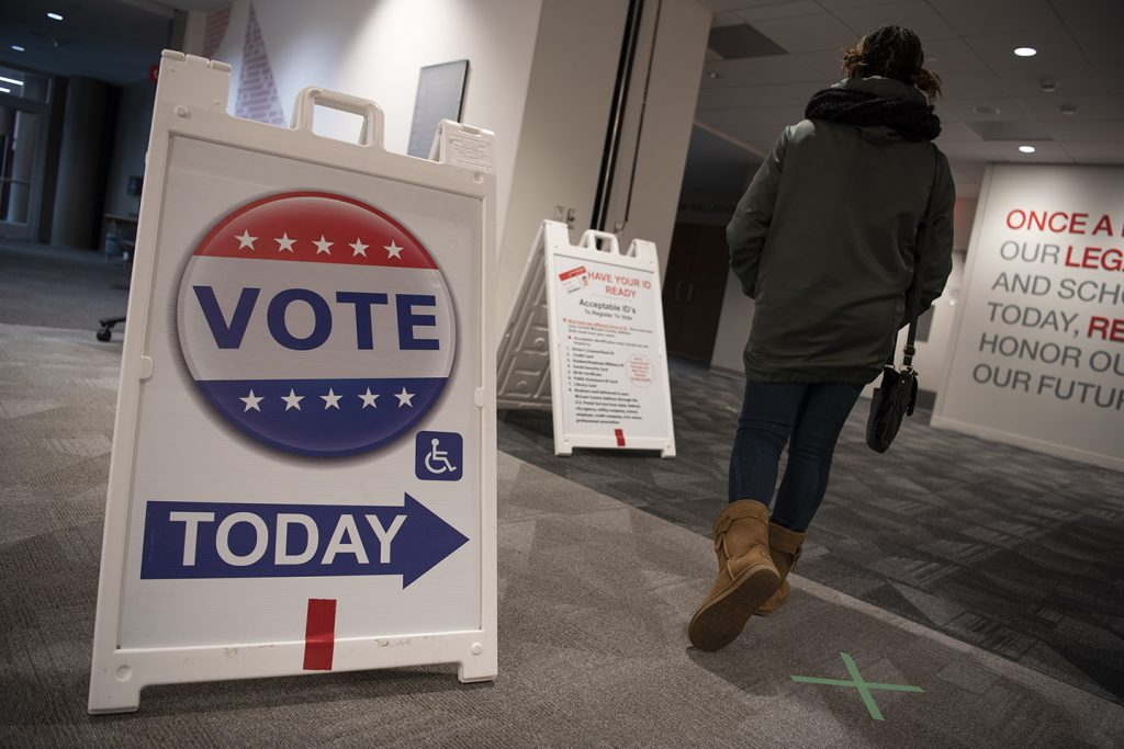 Student walks in room to vote with a voting sign in the foreground