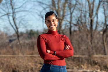 Mahogany West stands in front of a lake