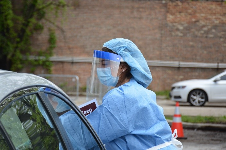 Woman in nurse suit, face shield, and face mask reaches into car at testing site