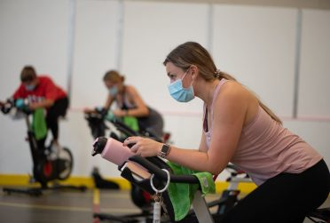 girl wearing mask on stationary bike
