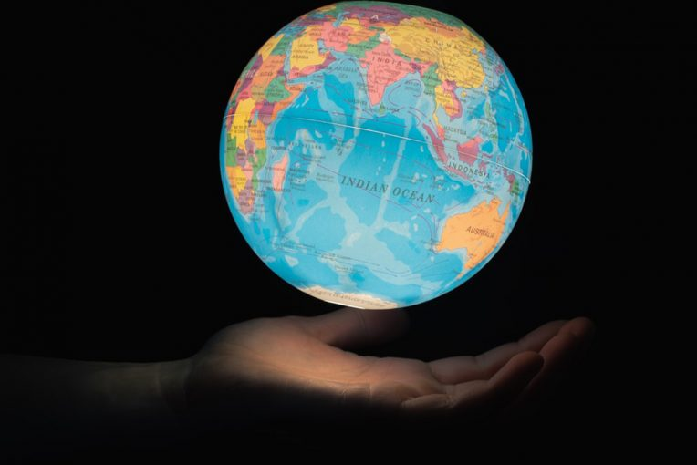 A photo of a hand under a lit up globe
