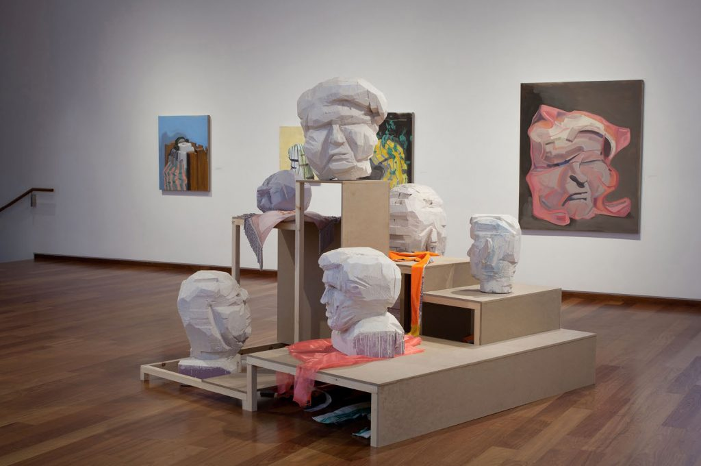 Jason Duda. Installation view of A hall of unflattering portraits depicting 2D and 3D artwork.
