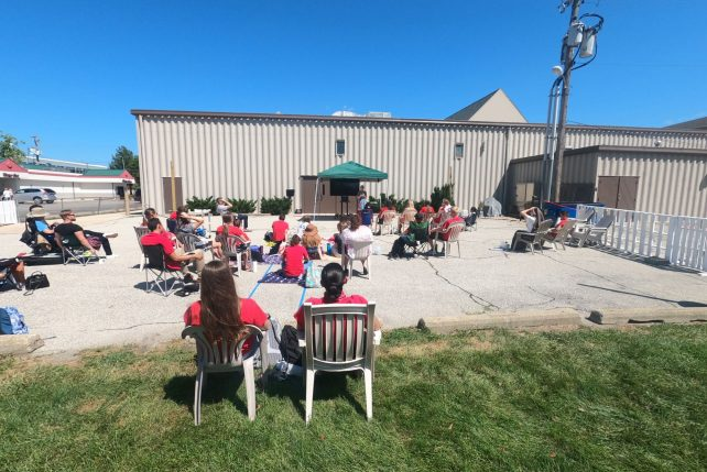 Students socialize outdoors at the St. Paul John II Newman Center