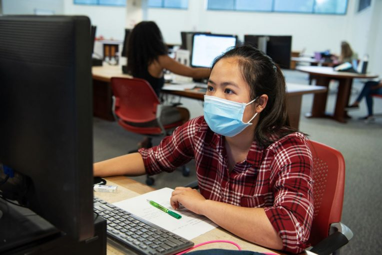 Student wearing a mask using a computer on Milner Library's second floor