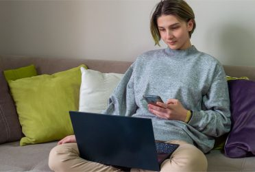 Student on couch with laptop and smartphone