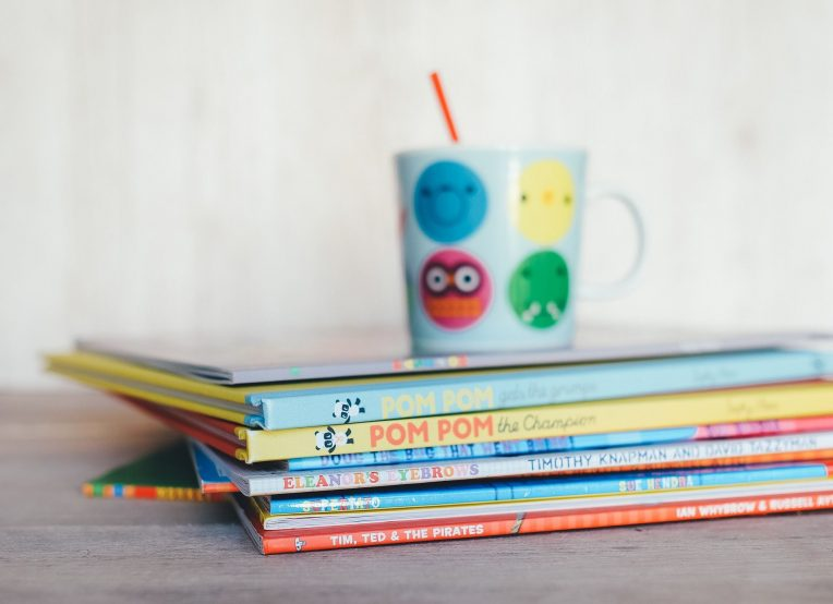child's cup on a stack of children's books