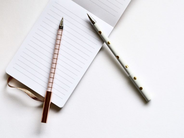Two pens on notebook and a table